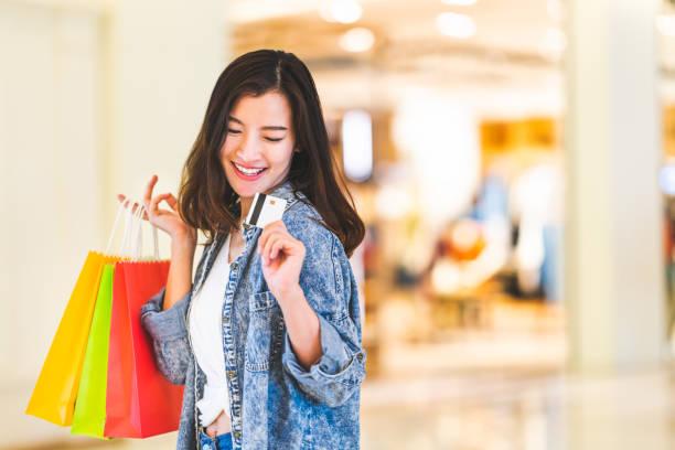 クレジット カードで美しいアジアの女性の幸せな笑顔は、ショッピング バッグ、ショッピング モールの背景にコピー スペースを保持します。買い物中毒の人、金持ちの女の子お金生活習慣 - 買い物 ストックフォトと画像