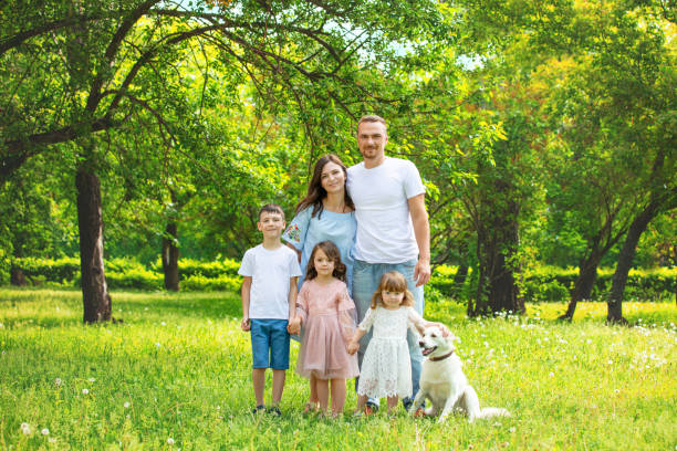 Happy beautiful big family together mother, father, children and dog walking on a Sunny summer day stock photo