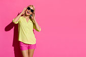 Happy beautiful blond woman in yellow shirt and pink shorts is standing, holding sunglasses, looking at camera and shouting. Three quarter length studio shot on pink background.