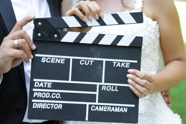Happy beautiful bride and groom, woman holds clapper board, cinema board stock photo