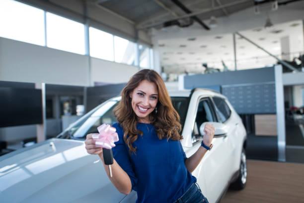 자동차 딜러 쇼 룸에서 새로운 차량 앞에 차 열쇠를 들고 행복 한 아름 다운 갈색 머리 여자. - 새로운 뉴스 사진 이미지