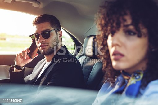 627863858istockphoto Happy beautiful business people sitting in the car driving and working together. 1154340647