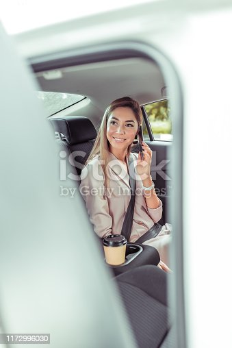 istock Happy beautiful business woman sitting in a taxi phoning. An open door, guests will meet friends and girlfriends, a phone call, emotions of joy smile. The driver opens the door, car sharing. 1172996030