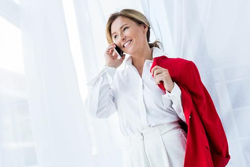 Glücklich Schöne Geschäftsfrau Halten Rote Jacke Und Per Smartphone Im Büro Sprechen Stockfoto und mehr Bilder von Arbeiten
