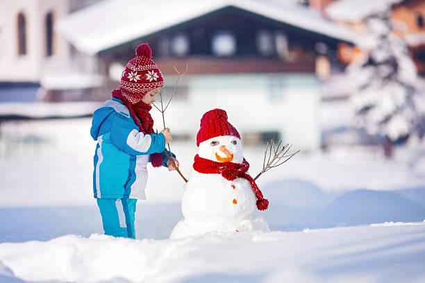 glückliche schöne kinder-gebäude schneemann im winter garden - schneemann bauen stock-fotos und bilder