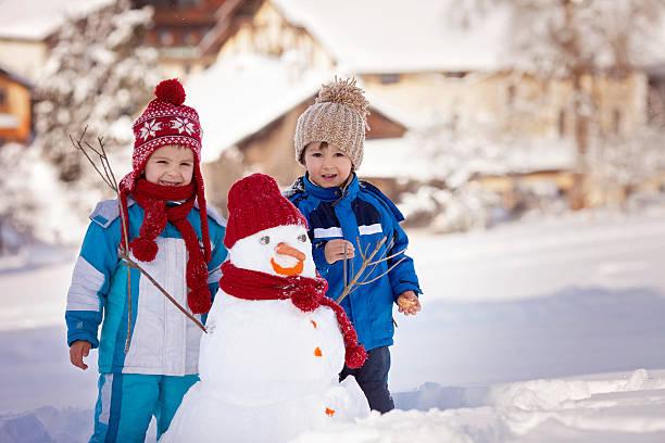 glückliche schöne kinder, brüder, gebäude schneemann im garten - schneemann bauen stock-fotos und bilder
