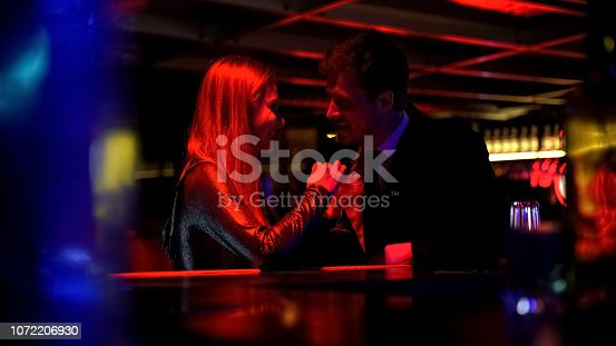 1072207668istockphoto Happy beautiful couple drinking cocktails and flirting in nightclub, romance 1072206930