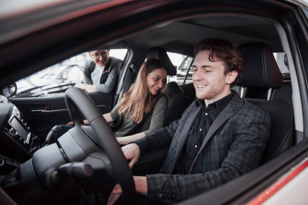 happy beautiful couple is choosing a new car at dealership - used car selling stock pictures, royalty-free photos & images