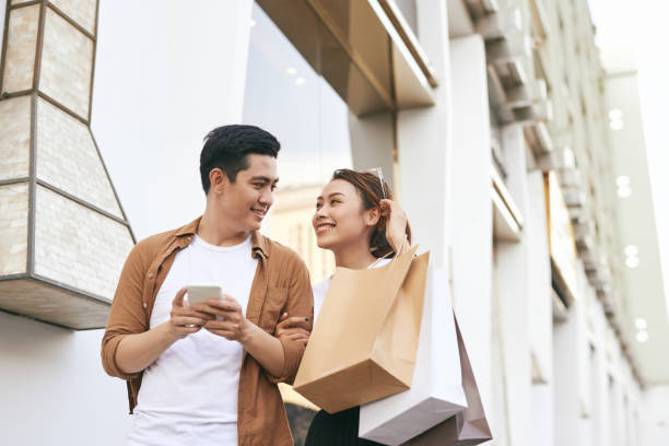 Happy beautiful couple using smart phone and shopping together. Happy beautiful couple using smart phone and shopping together. shopping couple asian stock pictures, royalty-free photos & images