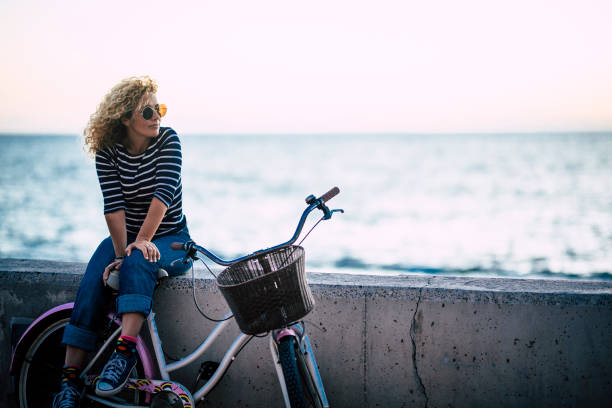 Happy beautiful curly healthy caucasian adult middle age woman sit down on a vintage coloured bike and enjoy the ocean in outdoor leisure activity - trendy people with hapy life stock photo