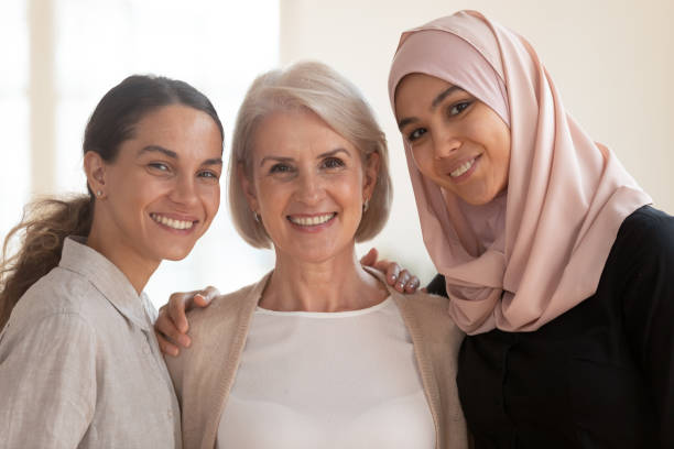 Happy beautiful diverse two generation women bonding looking at camera Three happy beautiful diverse two generation women young asian muslim woman wear hijab and caucasian older mature female multicultural ladies bonding standing together looking at camera, portrait religious veil stock pictures, royalty-free photos & images