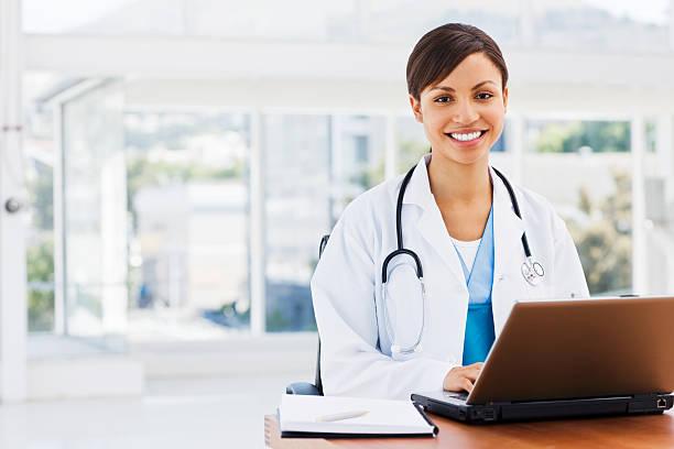 Glückliche schöne Doktor sitzend mit einem laptop – Foto