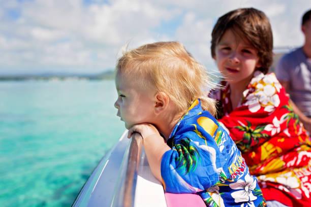 Feliz familia de la moda hermosa, niños y padres, vestidos con camisas hawaianas, disfrutando de un viaje de un día con lancha rápida - foto de stock