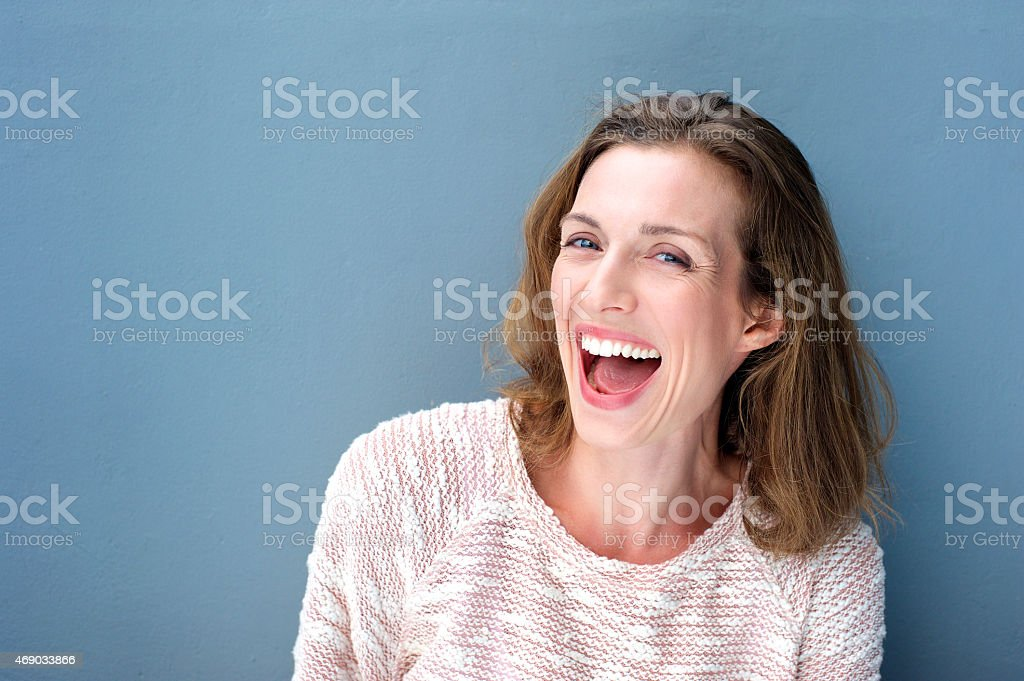 Happy beautiful fresh mid adult woman laughing stock photo