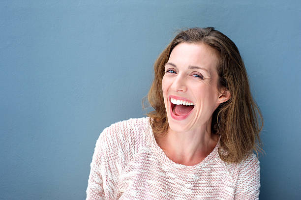 happy beautiful fresh mid adult woman laughing - mid adult women stock pictures, royalty-free photos & images