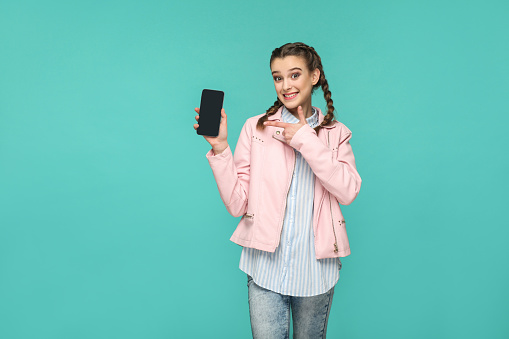 istock happy beautiful girl in casual or hipster style, pigtail hairstyle, standing, holding and pointing at mobile display, screen with toothy smile 1031503940