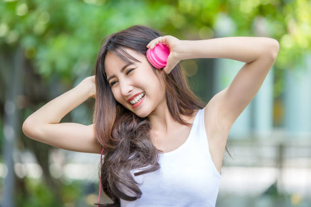 Happy beautiful girl listening to the music with her pink headphones stock photo