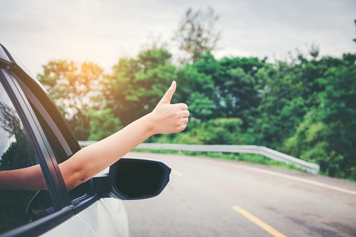 istock Happy beautiful girl traveling in a hatchback car 802921282