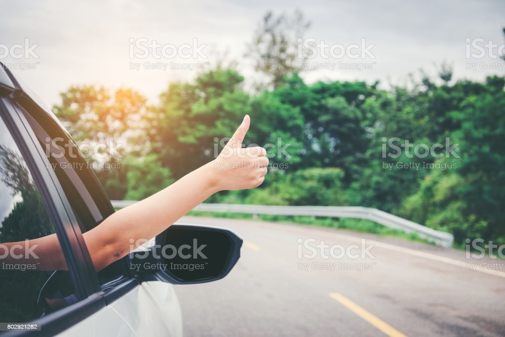 Happy beautiful girl traveling in a hatchback car stock photo