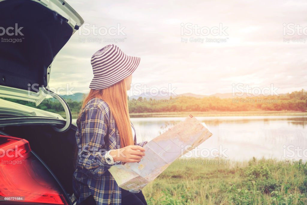 Happy beautiful girl traveling in a hatchback car with map stock photo