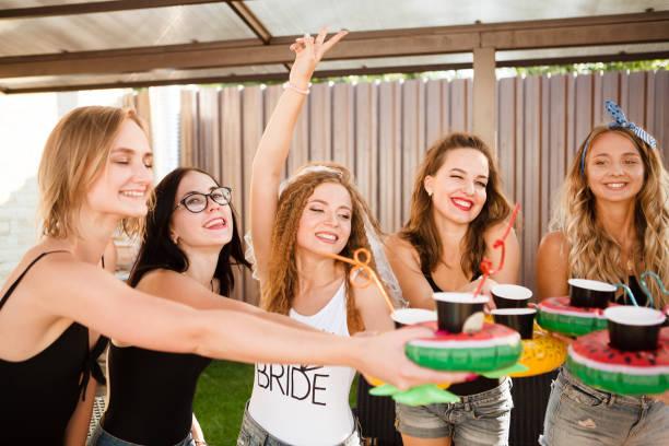 glücklich schönen freundinnen champagner trinken und eine tolle zeit auf bachelorette party im freien. - outdoor braut duschen stock-fotos und bilder