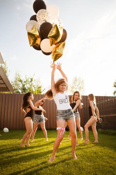 glücklich schönen freundinnen mit luftballons haben eine tolle zeit bei den junggesellinnenabschied. attraktive junge frauen braut tanzt mit freundinnen im freien. - outdoor braut duschen stock-fotos und bilder
