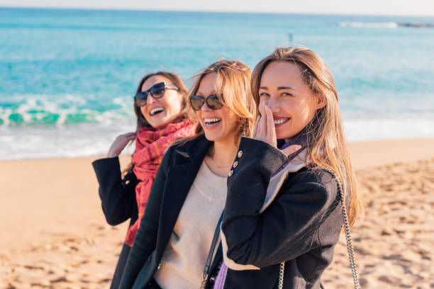 Happy beautiful girls having fun on winter beach (Barcelona, Spain) - three women friends laughing together - female friendship concept