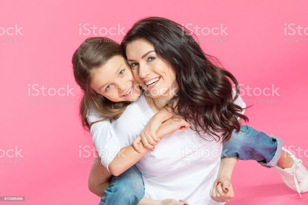 Happy beautiful mother and daughter hugging and smiling at camera stock photo