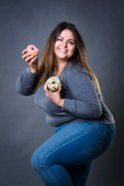 happy beautiful plus size model in jeans posing with donuts - big cake stock photos and pictures