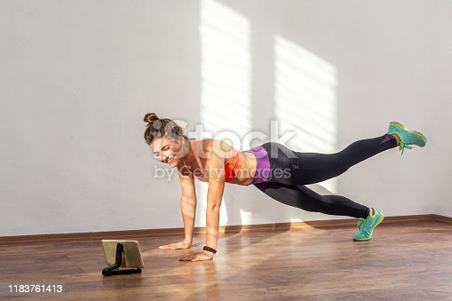 Happy beautiful sporty woman with bun hairstyle and in tight sportswear doing plank with leg raise while watching training video on tablet. indoor studio shot illuminated by sunlight from window