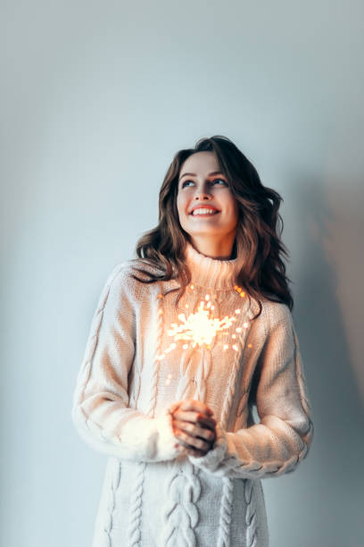 happy beautiful woman holding festive sparkler - excited emoji stock photos and pictures
