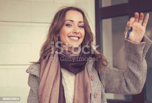 istock Happy beautiful woman holding keys from her new apartment 886658804