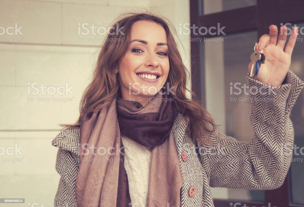 Feliz bella mujer sosteniendo las llaves de su nuevo apartamento - foto de stock