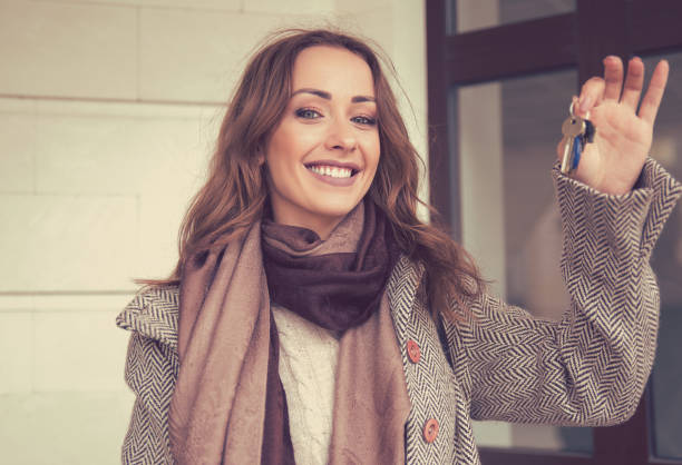 Happy beautiful woman holding keys from her new apartment - foto stock