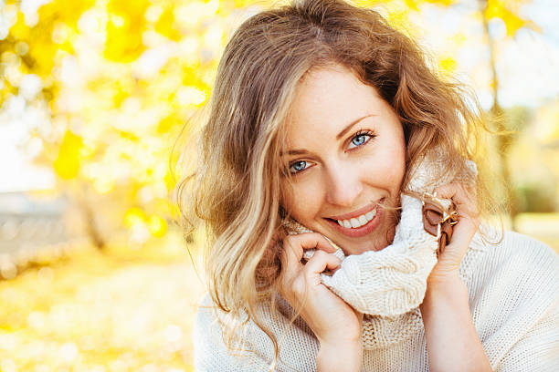 Happy beautiful woman in autumnal park stock photo
