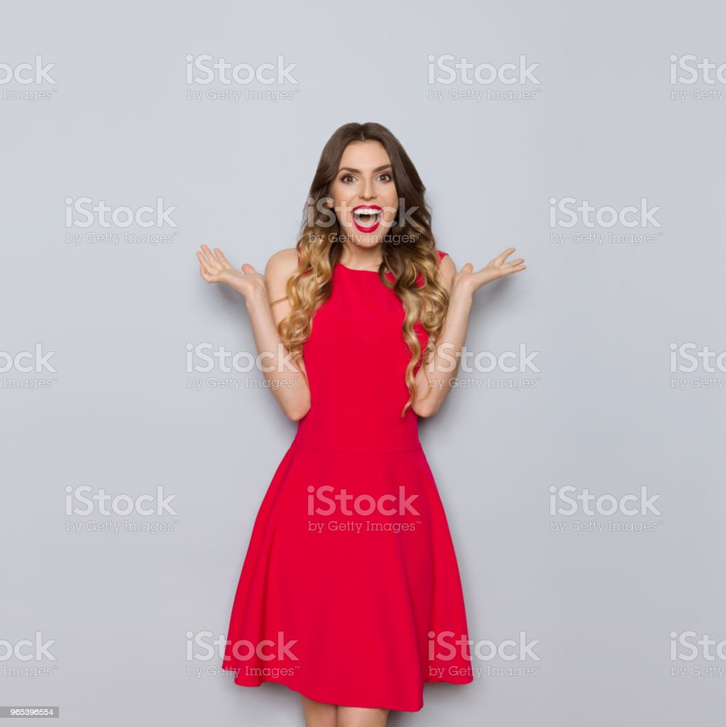 Happy Beautiful Woman In Red Dress Is Shouting And Gesturing zbiór zdjęć royalty-free
