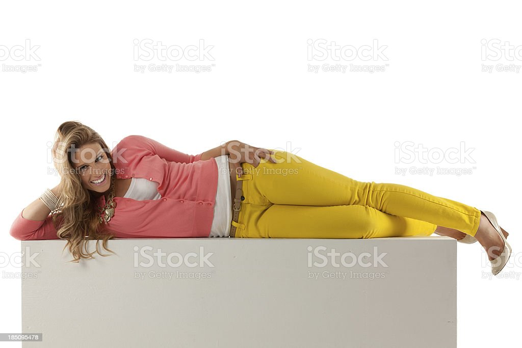 Happy beautiful woman lying on a wall stock photo