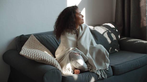 glückliche schöne frau auf sofa in decke entspannen zu hause gewickelt. - cozy stock-fotos und bilder