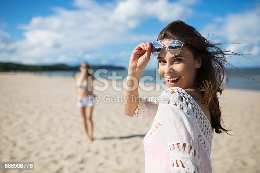 istock Happy beautiful woman standing on beach with friend laughing 666908776