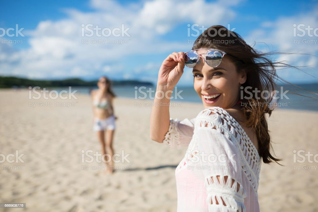 Happy beautiful woman standing on beach with friend laughing stock photo