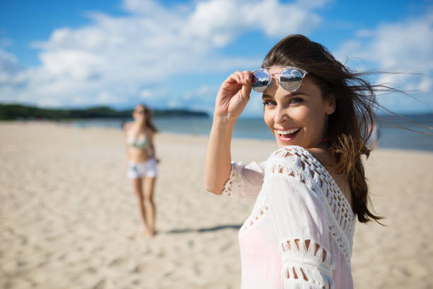 happy beautiful woman standing on beach with friend laughing - beach fashion stock photos and pictures