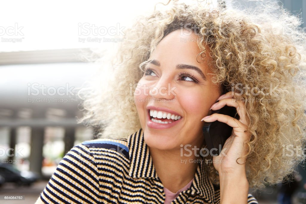 Happy beautiful woman talking on mobile phone stock photo