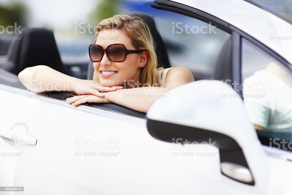 Happy, beautiful woman wearing sunglasses and resting at car door royalty-free stock photo