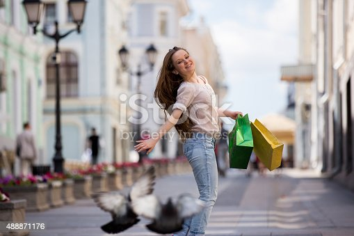 615594632 istock photo Happy beautiful woman with shopping bags 488871176