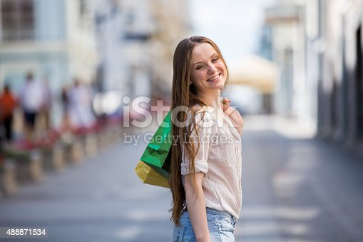 615594632 istock photo Happy beautiful woman with shopping bags 488871534