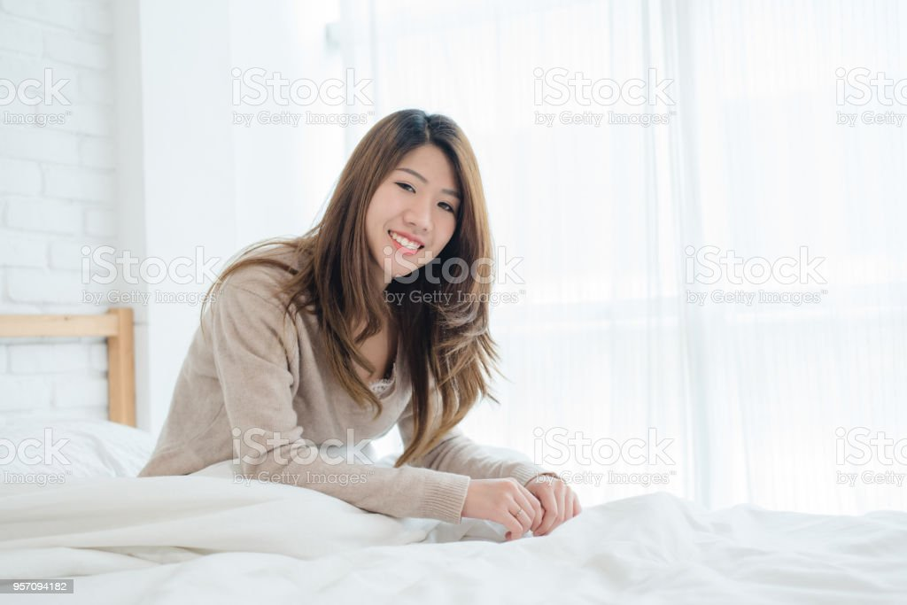 Happy beautiful young Asian woman waking up in morning, sitting on bed, stretching in cozy bedroom, looking through window. Funny asian woman after wake up. Asia woman is stretching and smiling. stock photo