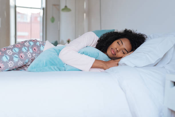Happy beautiful young black woman lying down in the bed sleeping