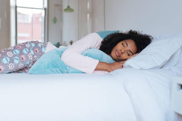 """gelukkig mooie jonge zwarte vrouw liggend in het bed slapen """"n - slapen stockfoto's en -beelden"""