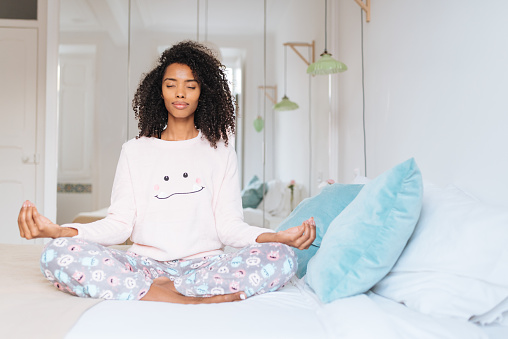 istock Happy beautiful young black woman relaxed  at home doing morning meditation in bed