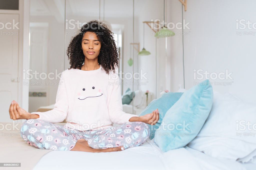 Happy beautiful young black woman relaxed  at home doing morning meditation in bed 'n stock photo
